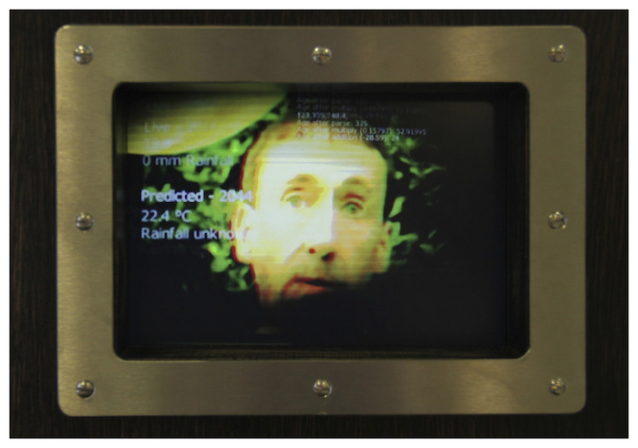 a face and weather data appearing on the screen