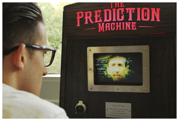 a man looking at the screen and lit up sign of The Prediction Machine