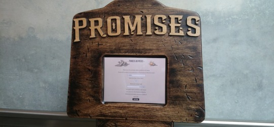 The top of the Promises and Wishes Machine with a screen and a sign saying 'Promises'